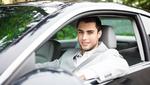 chico joven conduciendo coche gris