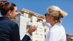 Dos Mujeres Observan Un Edificio Small
