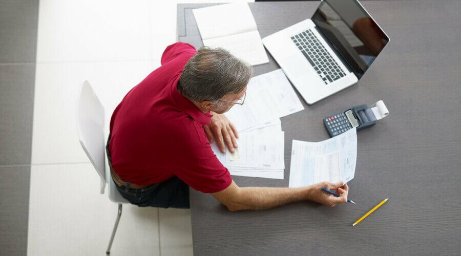 hombre repasa sus facturas con ordenador