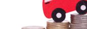 Un coche sobre monedas que representa el ahorro en seguros de vehículos
