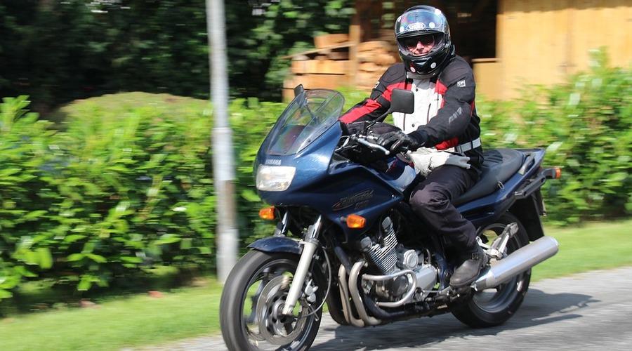 Un motorista bien uniformado y con su casco está dando un paseo en moto