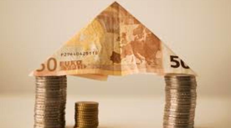 Una casa realizada con dos montones de monedas usados de pilares y un tejado de un billete de 50 euros