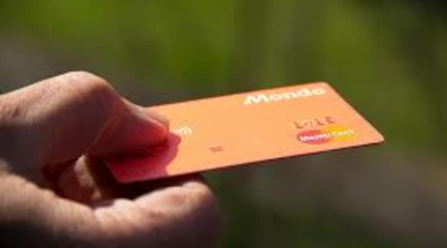 Un hombre sostiene una tarjeta de crédito en el mano