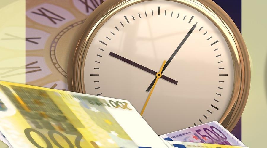 Un reloj marca la hora junto a varios billetes
