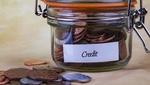 """Un bote en el que pone """"crédito"""" está lleno de monedas"""