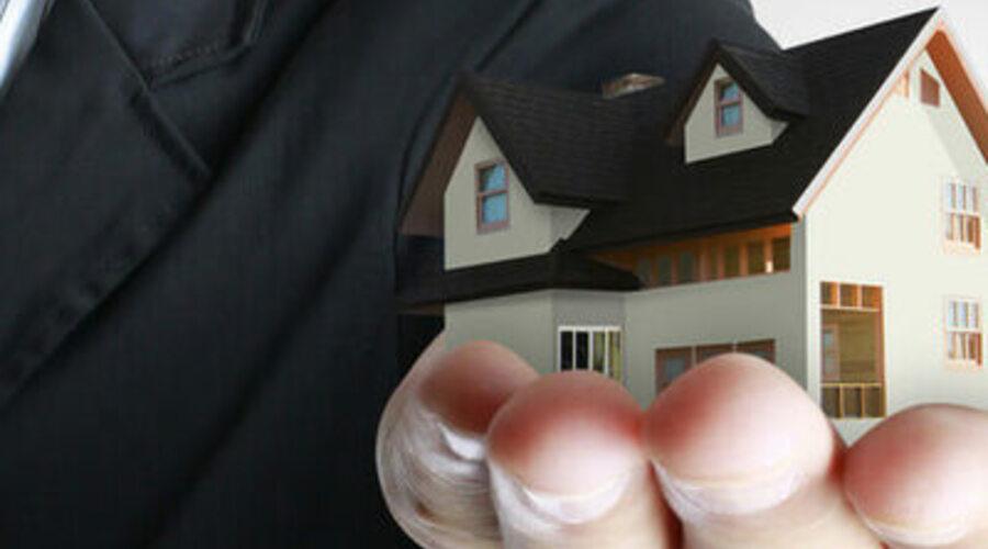 La mano de un hombre sujeta una maqueta de una casa