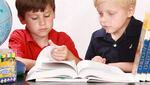 Dos niños están pasando páginas por un libro